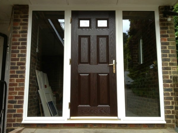 Darkwood GRP composite front door with white a uPVC outerframe glazed with clear toughened glass. (2)